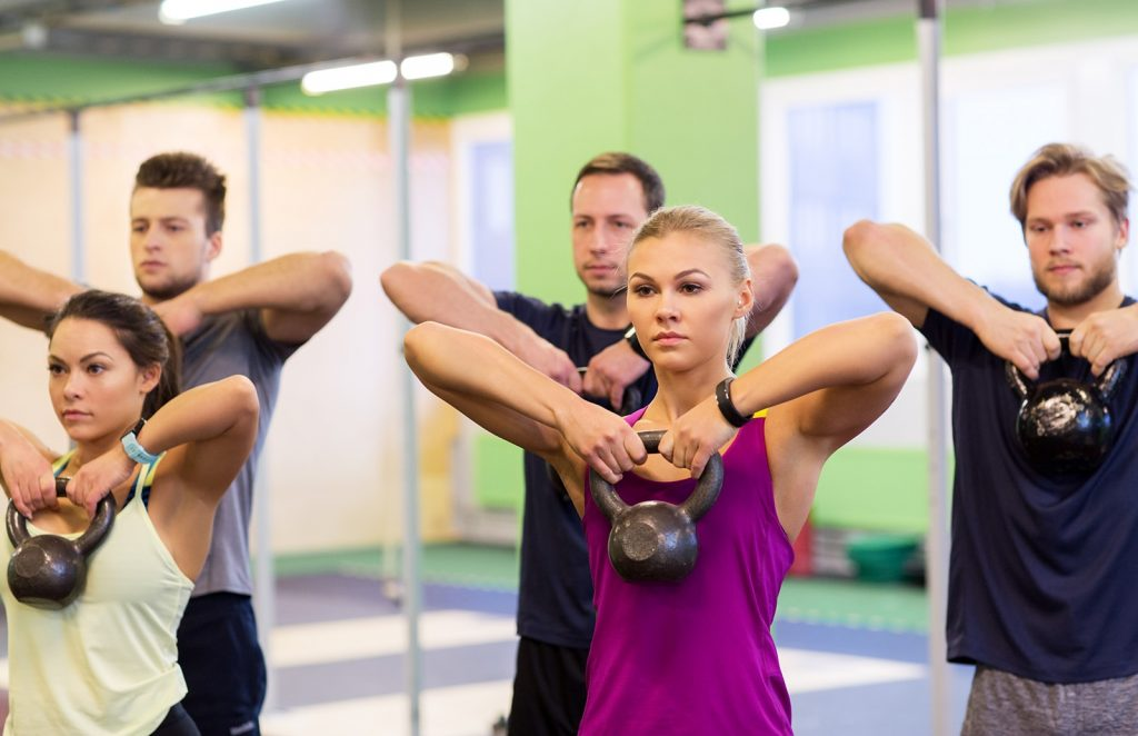 Group Of People With Kettlebells Exercising In Gym Pvuycnm