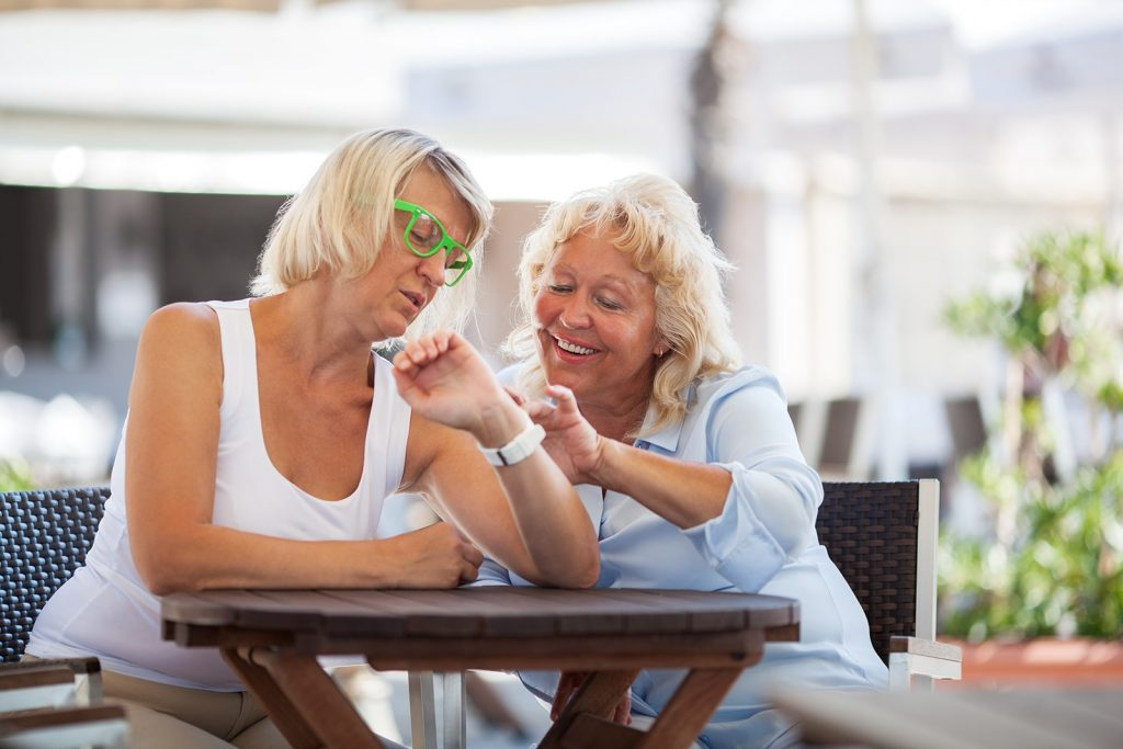 Mature Women Using Smart Watch In Street Cafe Raxud6v