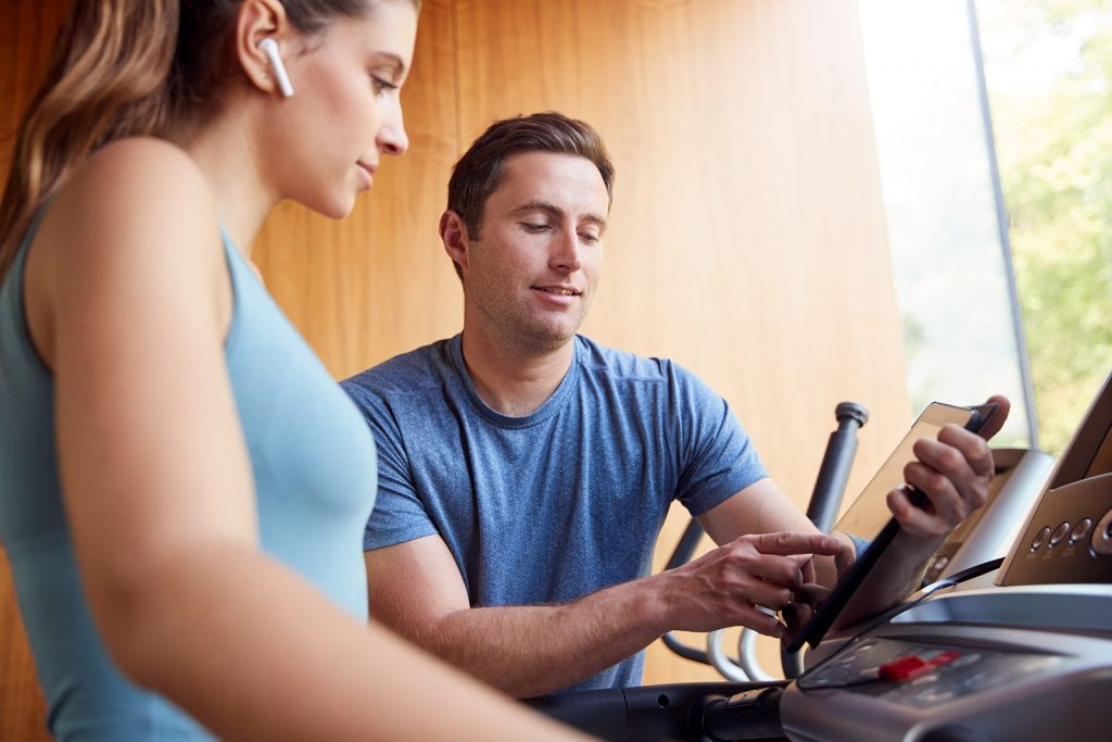 Woman In Gym With Personal Trainer Analysing Perfo Tblsauw